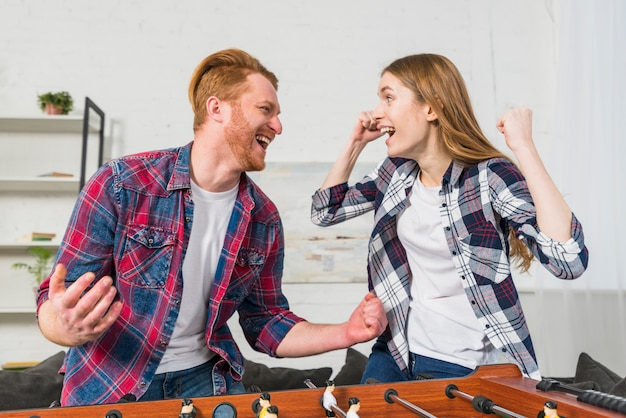 Successful young couple enjoying playing the table soccer game at home