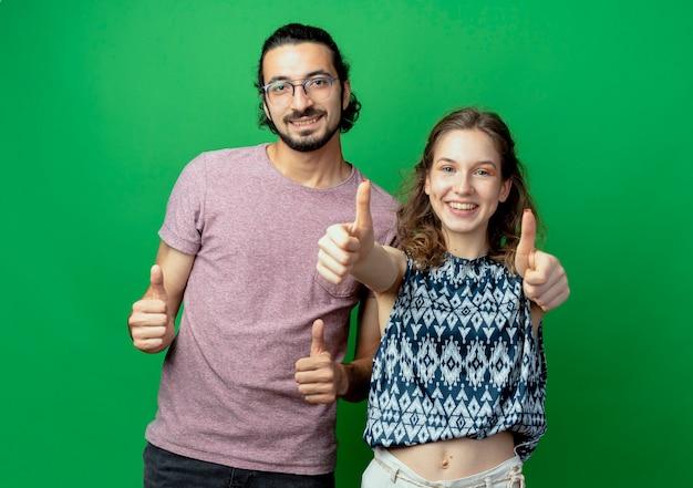 Успешная молодая пара мужчина и женщина, глядя в камеру, весело улыбаясь, показывает палец вверх на зеленом фоне