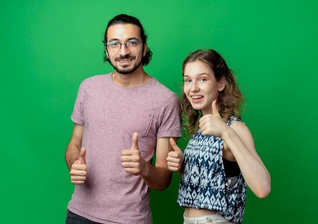 Успешная молодая пара мужчина и женщина весело улыбаются, показывая палец вверх над зеленой стеной