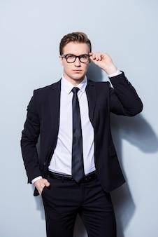 Успешный молодой красивый бизнесмен-банкир в костюме поправляет очки, он стоит на чистом светлом пространстве. такой зрелый и мужественный, горячий и уверенный