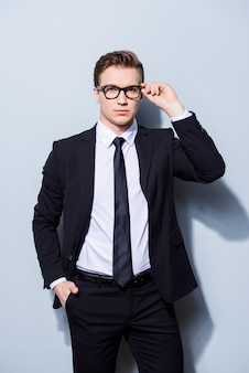 Successful young handsome businessman banker in a suit is fixing his glasses, he stands on pure light space. so mature and virile, hot and confident