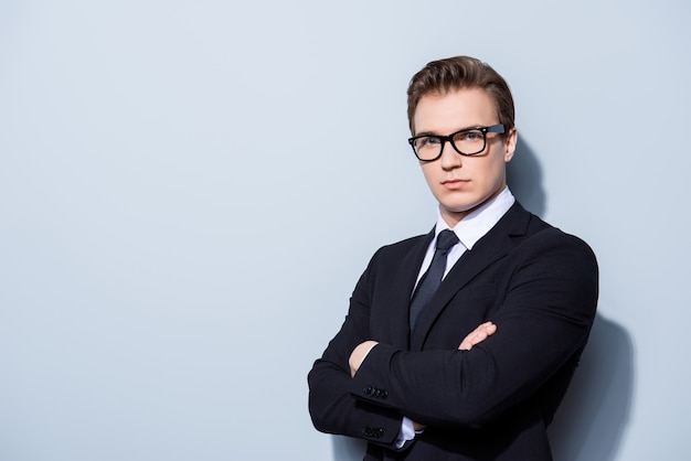 Successful young handsome man lawyer in a suit and glasses on pure space with crossed hands. severe and harsh, rich and confident, attractive and smart