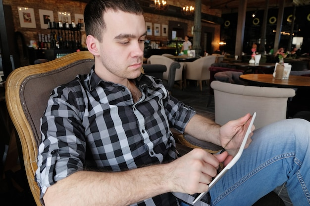 A successful young man in a dark plaid shirt in the cafe does business. young hipster holding in arms digital tablet. office worker on lunch.
