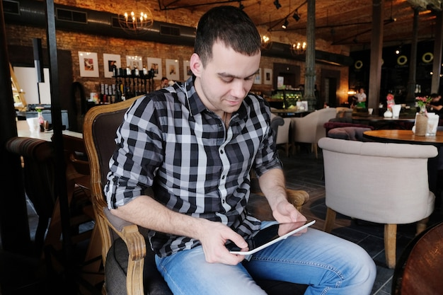 A successful young man in a dark plaid shirt in the cafe does business. young hipster holding in arms and looking at digital tablet, smiling. office worker on lunch.