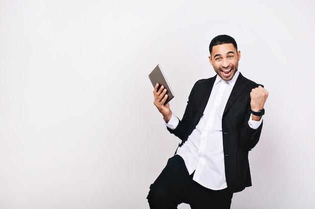 白いシャツ、成功を表現する黒いジャケットで成功した若い男。リーダーシップ、素晴らしいキャリア、マネージャー、陽気な気分、幸運、笑顔。
