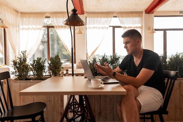 Успешный молодой человек сидит за столиком в офисе возле окон и работает на ноутбуке во время обеденного перерыва за чашкой кофе. фрилансер