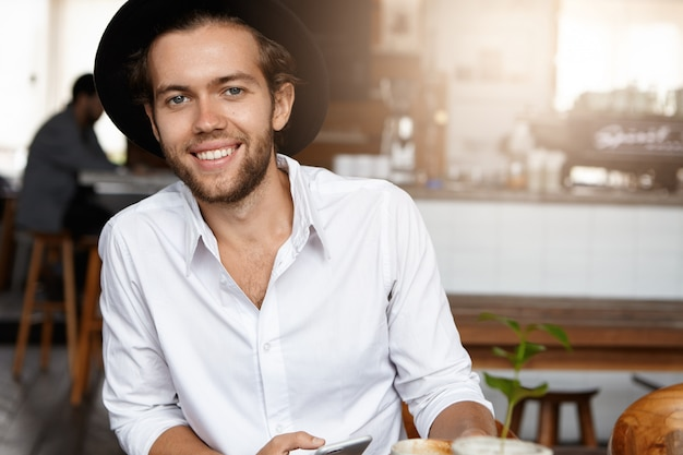 Successful young man in stylish hat relaxing alone at cozy cafeteria during lunch break, looking with happy expression