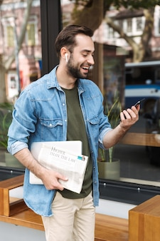 Successful young man wearing earpods using smartphone while walking through city street with newspaper and laptop in hand