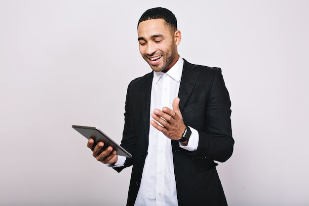 Successful young man in white shirt, black jacket smiling to tablet in hands. leadership, great career, manager, cheerful mood, office work, modern technology, smiling.