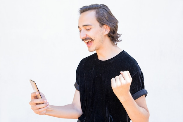 Successful young man with handlebar mustache using phone.