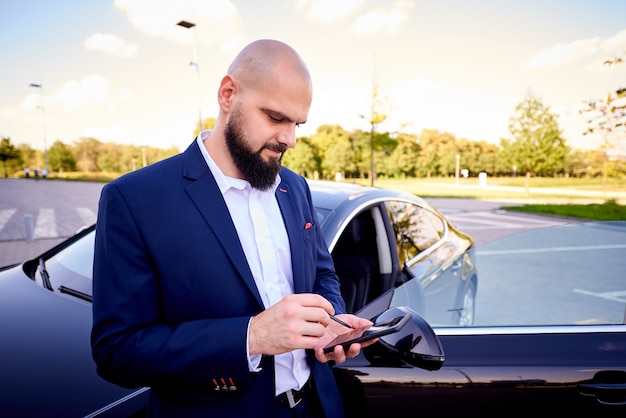 Successful young man with a phone near a auto in a parking lot.