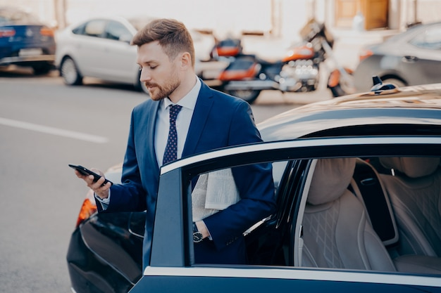 Успешный молодой ухоженный исполнительный менеджер в строгом стильном костюме выходит из автомобиля премиум-класса, прибывает на рабочее место и проверяет пропущенные звонки в своем мобильном телефоне. деловые люди на открытом воздухе