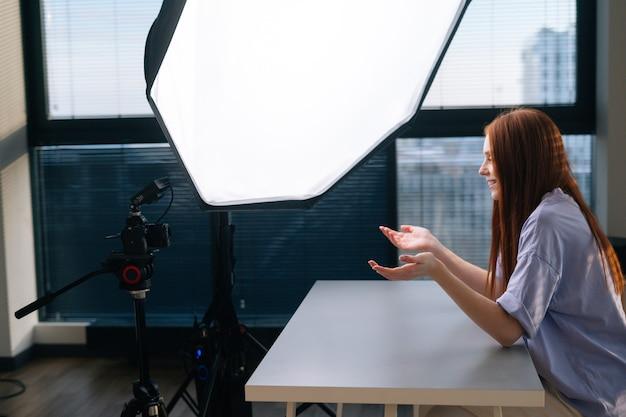 책상에 앉아 카메라와 소프트박스를 사용하여 비디오 vlog를 녹화하는 성공적인 젊은 여성 블로거