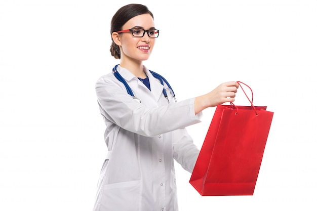 Successful young woman doctor with stethoscope giving shopping bag in white uniform on white