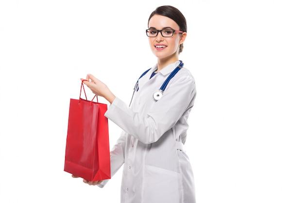 흰색 유니폼에 청진기를 제공하는 쇼핑 가방과 함께 성공적인 젊은 여자 의사