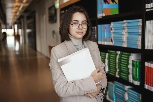 성공적인 젊은 여성이 대학에 등록하고 열심히 공부하고, 프로젝트에서 작업하고, 문서를 들고, 홀에 책 더미 근처에 서서 편안한 표정으로 카메라를 웃고 있습니다.