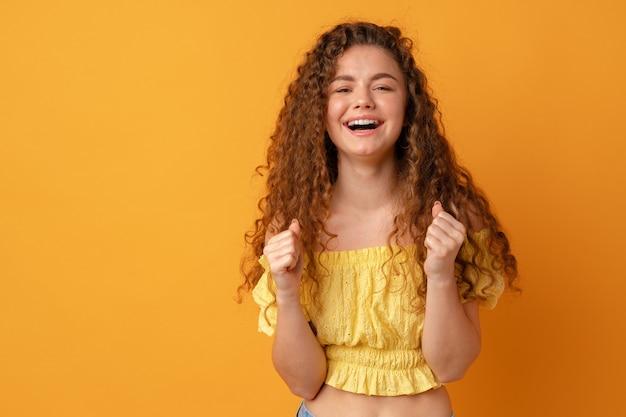 Успешная молодая женщина чувствует себя очень взволнованной и поднимает руки