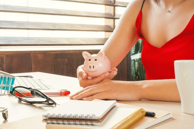 Успешная молодая женщина держит розовый копилку в руках, сидя в офисе