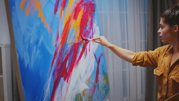 Successful young woman painting in her home studio.
