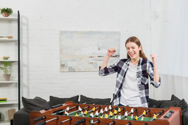 Successful young woman standing near the table soccer game clenching her fist
