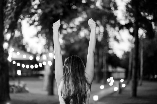 両腕を上げて勝利した成功した若い女性。黒と白