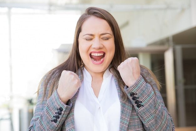 Successful young woman with raised fists