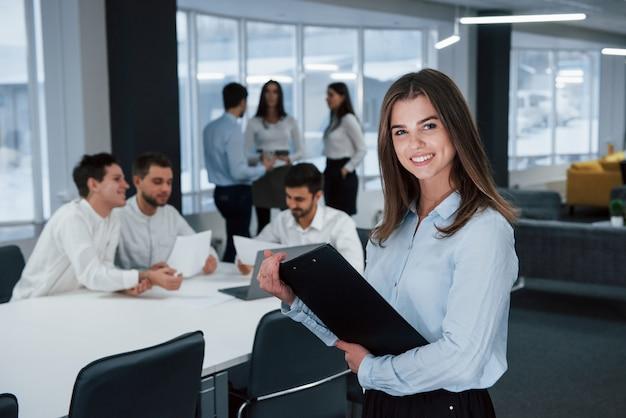 成功した若者。バックグラウンドで従業員とオフィスに立っている若い女の子の肖像画