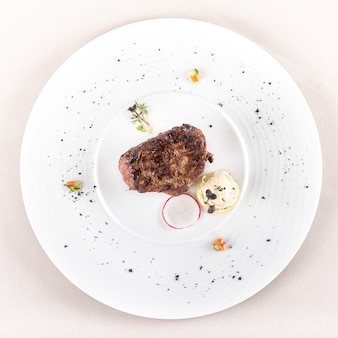 Succulent beef tenderloin steak,  served with butter with herbs, decorated with radish