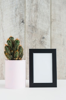 Succulent plant in container near the blank picture frame on desk against wooden wall