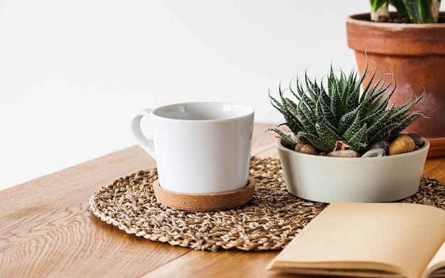 Succulent in a pot, white mug, notepad on a wooden table in a scandinavian interior. houseplant. copy space.