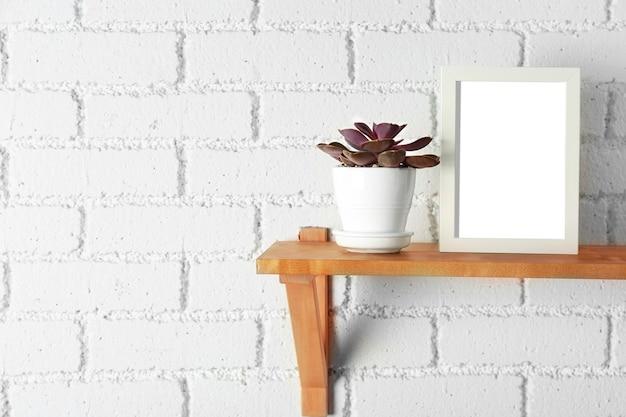 白いレンガの壁の木製の棚にフォトフレームと多肉植物