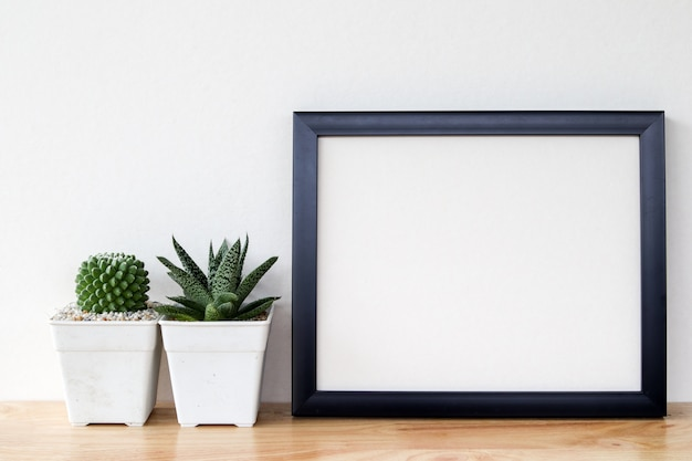 Succulents or cactus in concrete pots over white background on the shelf and mock up frame photo