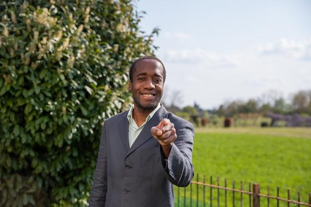 우리가 원하는대로 그의 손가락으로 카메라를 가리키는 성공적인 아프리카 사업가.