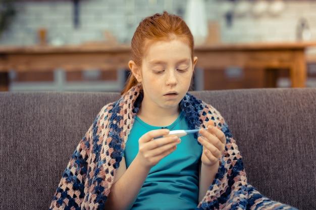 Такая лихорадка. грустная больная девушка смотрит на термометр, страдая от высокой температуры