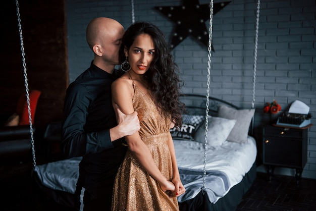 Такая прекрасная пара. пара в классической одежде стоит перед красивой роскошно украшенной кроватью