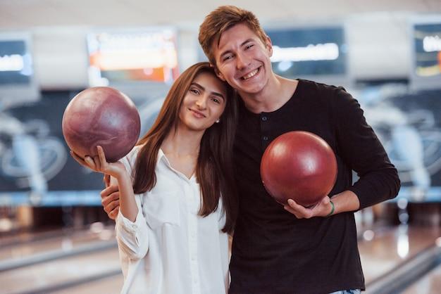 そんな素敵な人たち。手でボウリングのボールを保持している幸せなカップルとクラブで楽しい時間を過ごす