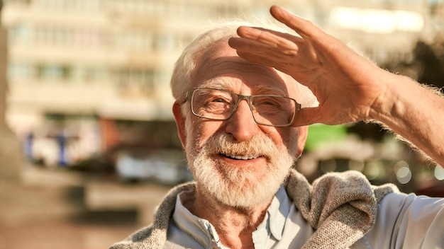 Such a great day portrait of happy and handsome bearded senior man in glasses looking at camera and