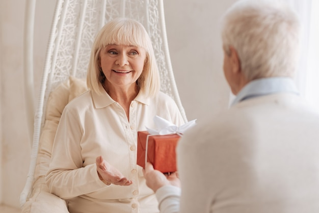 Such a surprise. cheerful delighted senior woman smiling and looking at her husband while receiving a present from him