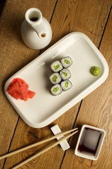 Суши и роллы на белой тарелке с соевым соусом