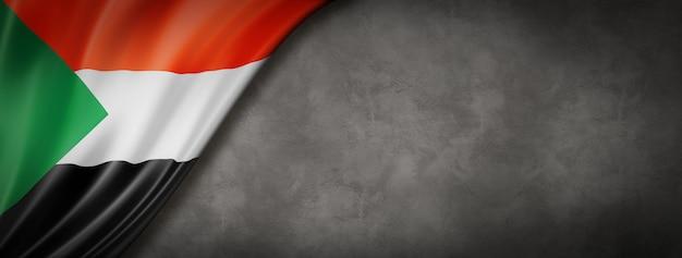 Sudan flag on concrete wall. horizontal panoramic banner. 3d illustration
