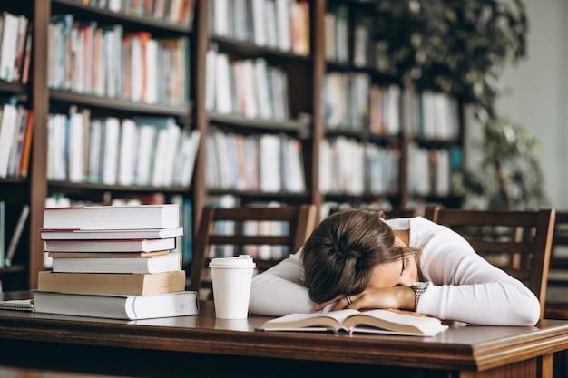 Судент спит в библиотеке на столе