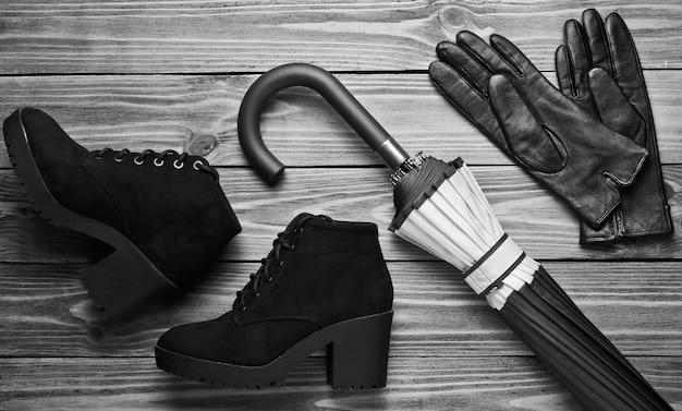 スエードの黒いブーツ、手袋、木の背景に傘。上面図。フラットレイ