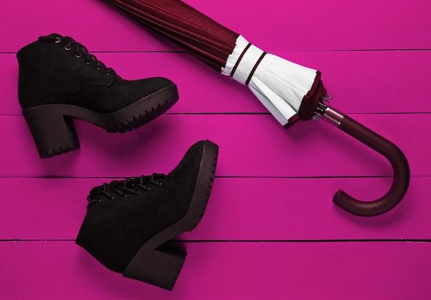 Замшевые черные сапоги, зонтик на розовом деревянном фоне. вид сверху