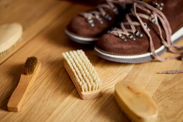 Замшевые сапоги и аксессуары по уходу на деревянном столе