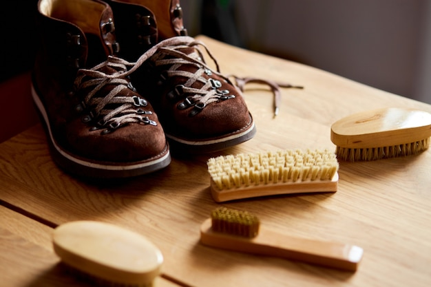 Suede boots and care accessories on wooden table