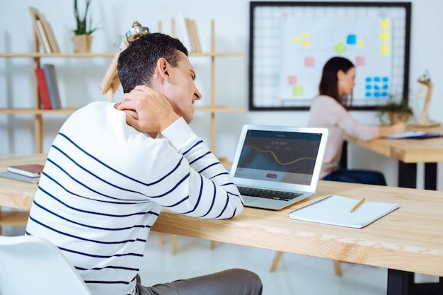 고통을 겪습니다. 컴퓨터 화면을 보면서 그의 목을 만지고 테이블에 팔을 두는 좌절 된 남자
