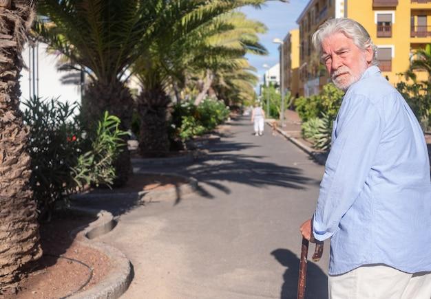 다리 통증에 대한 막대기의 도움으로 야외에서 걷는 고통받는 수염 난 노인