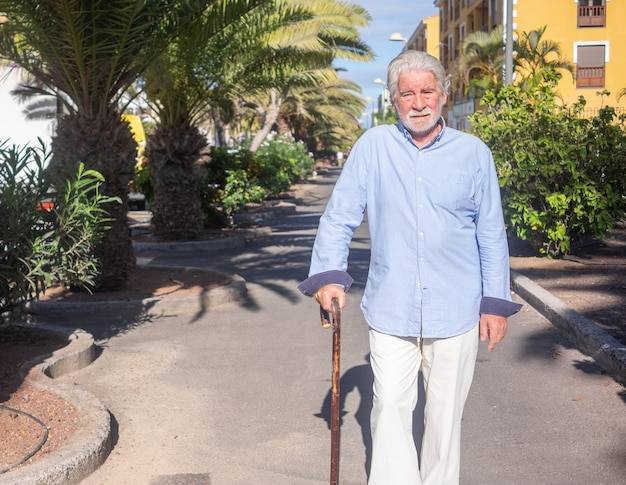 Suffering bearded senior man walking outdoors with help of a stick for legs pain