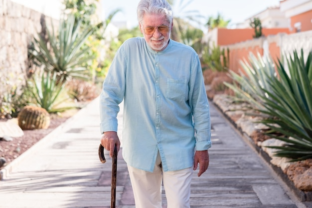 Suffering elderly man walking with the help of a cane. senior white haired people outdoor in a tropical garden