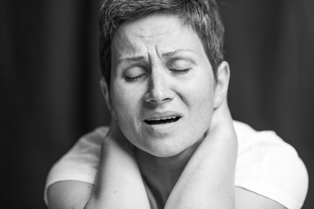 Suffering emotion on the face of an adult woman with a short gray hair. black and white portrait.